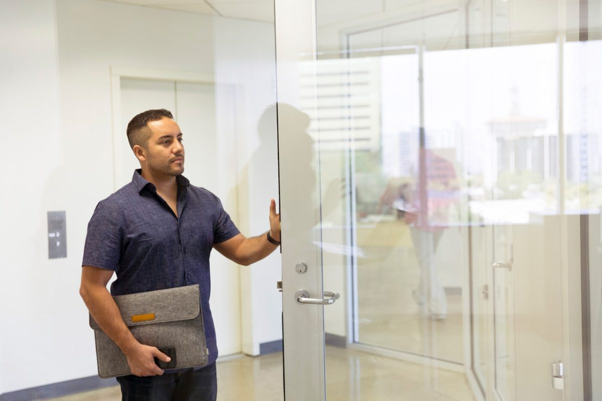 a man standing next to a glass door